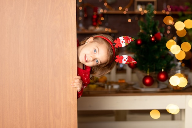 Wesoła dziewczynka wygląda zza drzwi w ciemnej kuchni z choinką na nowy rok lub boże narodzenie, uśmiechnięta i śmiejąca się w czapce świętego mikołaja, miejsce na tekst