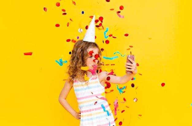 Wesoła dziewczynka z blond kręconymi włosami świętuje swoje urodziny. dziecko trzyma telefon, robi sobie selfie w deszczu konfetti. close-up portret na żółtym tle.