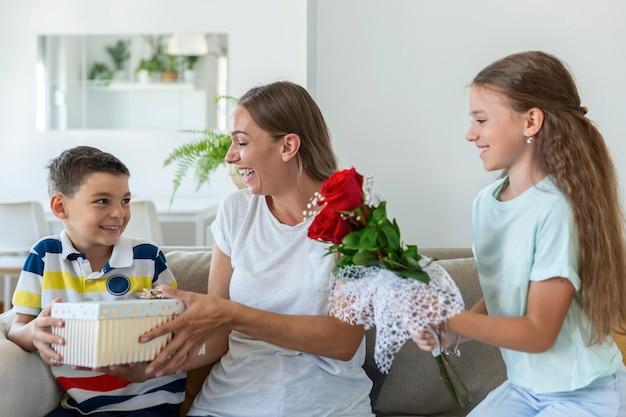 Wesoła dziewczynka z bukietem kwiatów róż i najmłodszy brat z pudełkiem uśmiecha się i gratuluje szczęśliwej mamy na dzień matki w domu. szczęśliwego dnia matki!