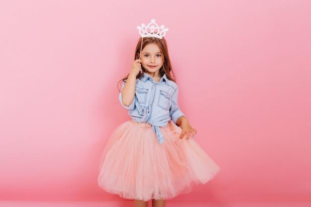 Wesoła dziewczynka z długimi brunetkami w tiulowej spódnicy, trzymając księżniczkę na głowie na białym tle na różowym tle. obchody wesołego karnawału dla dzieci, przyjęcia urodzinowego, zabawy z uroczym dzieckiem