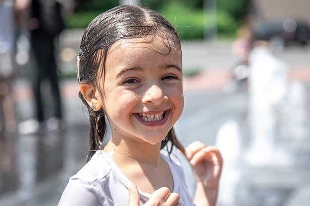 Wesoła dziewczynka z mokrymi włosami na zewnątrz w upalny letni dzień.