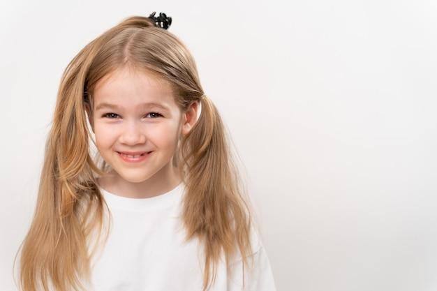 Wesoła dziewczynka z śmiesznie zebranymi włosami na białym tle. fryzury i fryzury dla dzieci. szampon i kosmetyki dla dzieci. kopiuj przestrzeń