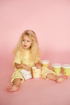 Wesoła dziewczynka z tacami z kolorowego papieru.
