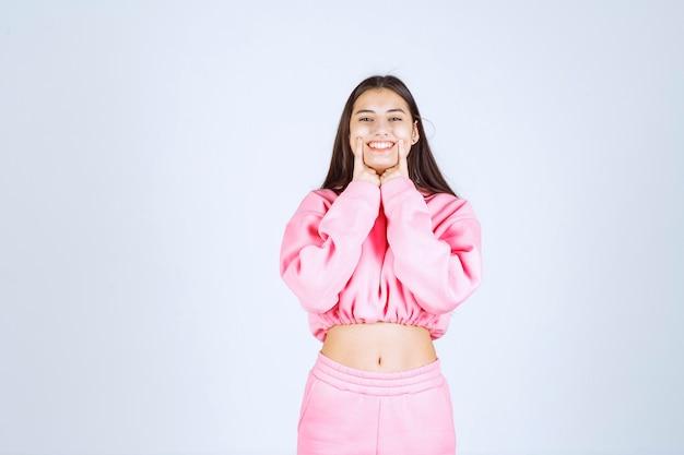 Wesoła ekspedientka w różowej piżamie promująca na scenie coś z zaufaniem
