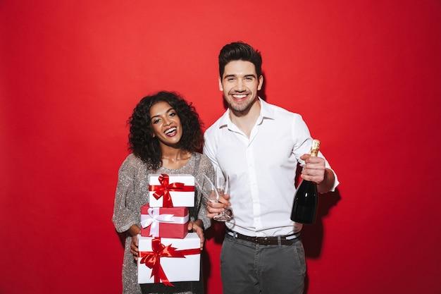 Wesoła, elegancko ubrana para stoi na białym tle nad czerwoną przestrzenią, świętuje nowy rok