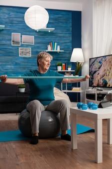 Wesoła emerytka pracująca mięśniami ramion przy użyciu gumki ćwiczącej ćwiczenia aerobowe