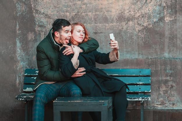 Wesoła, emocjonalna młoda para siedzi na ławce i robi selfie. dwóch szczęśliwych ludzi love story na ulicy