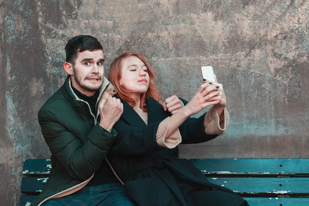 Wesoła emocjonalna młoda para siedzi na ławce i robi selfie