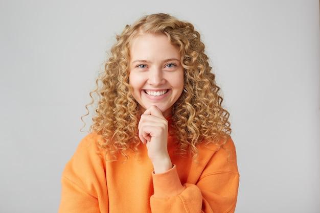 Wesoła emocjonalna szczęśliwa studentka uśmiecha się z przodu, demonstrując białe, idealne zęby