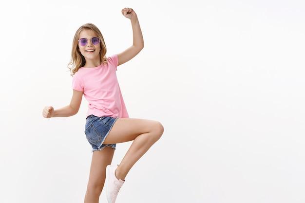 Wesoła, energetyzowana i charyzmatyczna mała blond dziewczynka w letnich okularach przeciwsłonecznych, różowa koszulka skacząca, unosząca nogę radośnie pozująca, tańcząca, bawiąca się, podnosząca ręce do góry rozbawiona, stojąca szczęśliwa biała ściana