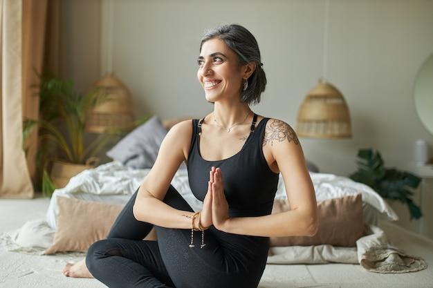 Wesoła, energiczna młoda kobieta siedzi skręcona kręgosłupem na podłodze w domu, robi ardha matsyendrasana podczas praktyki jogi