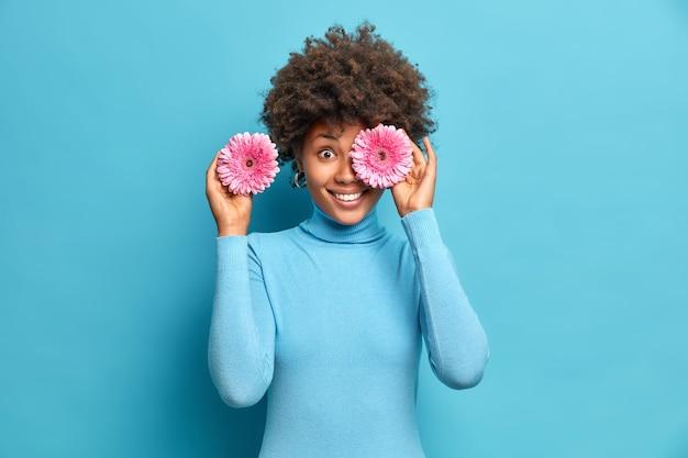 Wesoła etniczna kobieta trzyma gerbery przed oczami, uśmiecha się pozytywnie, cieszy się przyjemnym aromatem kwiatów