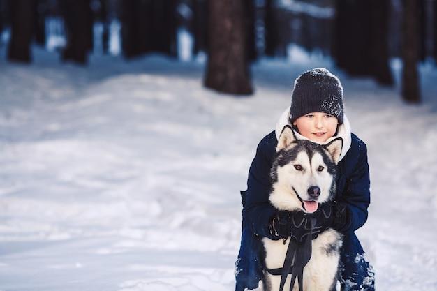 Wesoła europejska nastolatka przytula dużego psa zimą w lesie. pojęcie ferii zimowych. poziome zdjęcie.
