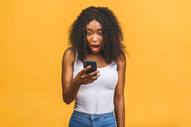 Wesoła falista czarnowłosa afroamerykanin czarna dziewczyna trzyma w rękach telefon na czacie w sieci