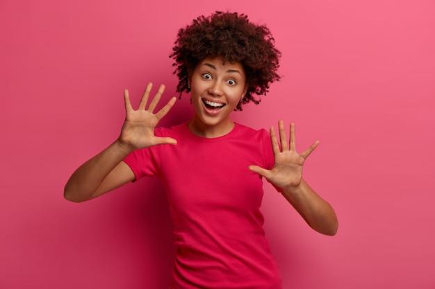 Wesoła, figlarna młoda kobieta gestykuluje obiema rękami, unosi dłonie, pokazuje dziesięć gestów, pozytywnie się śmieje, nosi różową koszulkę, stoi w domu, bawi się, oczy pełne szczęścia, głupcy w domu
