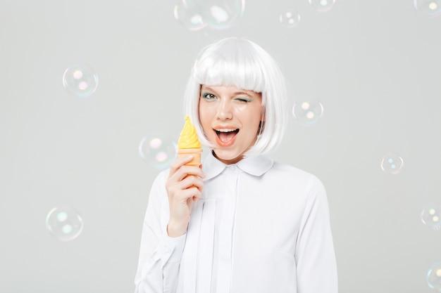 Wesoła figlarna młoda kobieta mruga i trzyma fałszywe lody