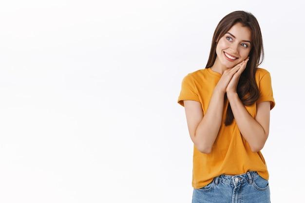 Wesoła, głupia i marzycielska romantyczna kobieta w żółtej koszulce, oparta twarz na dłoniach i patrząca w bok z zadowolonym, zamyślonym wyrazem twarzy, uśmiechnięta, marząca o czymś, białe tło