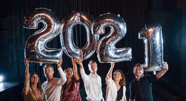 Wesoła grupa ludzi z napojami i balonami w rękach świętujących nowy rok 2021.