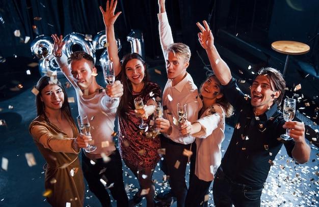 Wesoła grupa ludzi z napojami w rękach świętuje nowy 2021 rok.