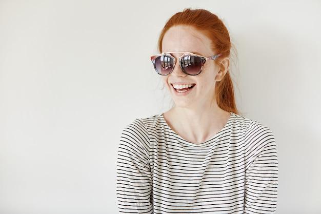 Wesoła hipster dziewczyna z piegami i rudymi włosami w stylowych odcieniach i marynarskiej koszuli uśmiechnięta radośnie, o pozytywnym nastroju, stojąca na białym tle