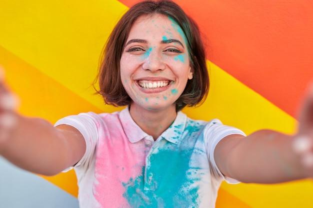 Wesoła hipster kobieta biorąc selfie podczas paint party