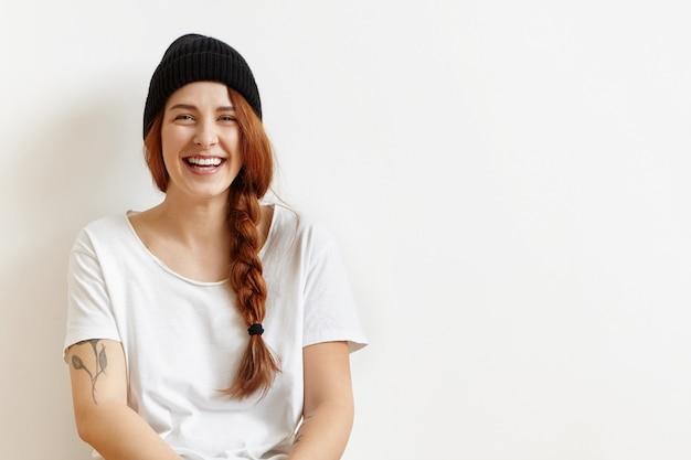 Wesoła hipster ruda dziewczyna ubrana w gruby warkocz na boku, siedząc na podłodze w białym pokoju