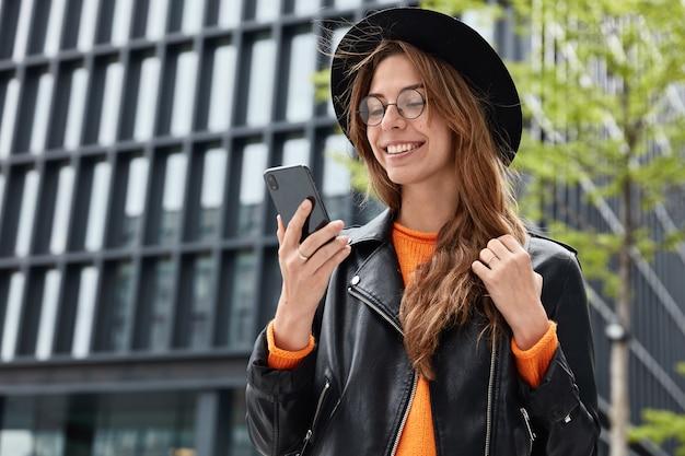 Wesoła hipsterka ubrana jest w stylowy czarny kapelusz, skórzaną kurtkę i okrągłe przezroczyste okulary