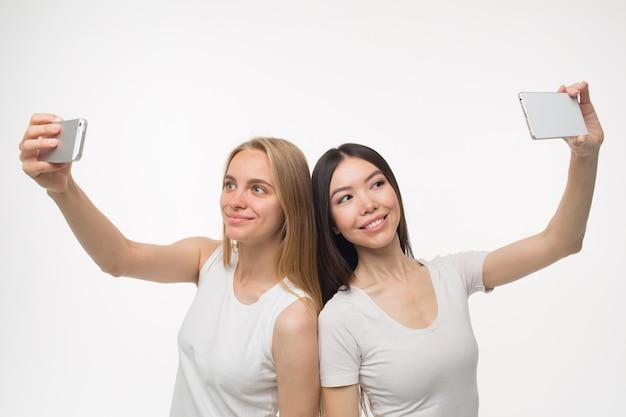 Wesoła i miła młoda kobieta stań do siebie i rób selfie