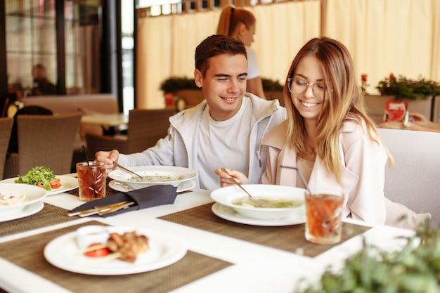 Wesoła i piękna para wypoczywa na letnim tarasie w restauracji z jedzeniem i napojami. facet i dziewczyna bawią się na tarasie