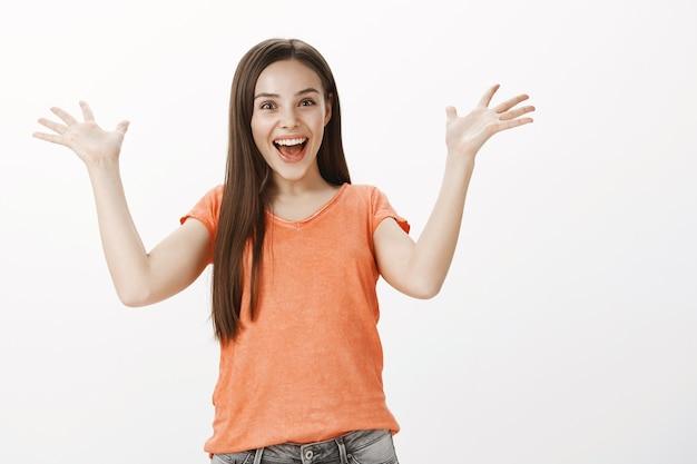 Wesoła i podekscytowana ładna dziewczyna raduje się, podnosi ręce z ulgą lub wdzięcznością, świętuje zwycięstwo