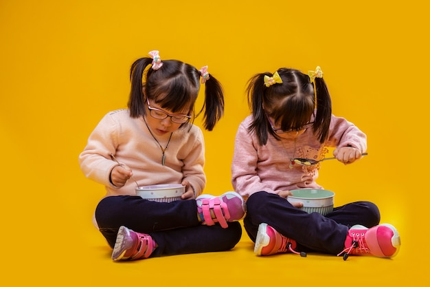 Wesoła i pozytywna. uważne, śliczne siostrzyczki siedzą na gołej podłodze i jedzą płatki z głębokich misek
