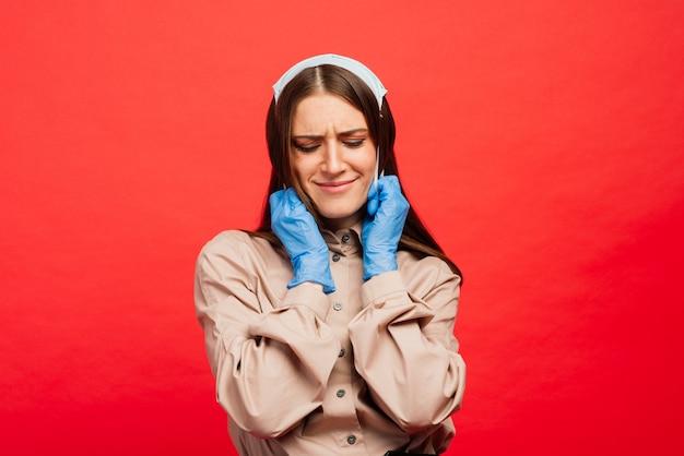 Wesoła i radosna młoda kobieta bawi się ochronną maską medyczną i niebieskimi rękawiczkami