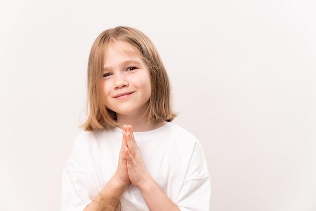Wesoła i szczęśliwa dziewczynka z quadem fryzury trzyma złożone ręce przed czaplą na białym tle. szczęśliwe dzieciństwo. witaminy i lekarstwa dla dziecka. pomyśl życzenie i uwierz w sen
