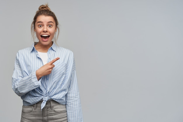 Wesoła i szczęśliwa kobieta o blond włosach zebranych w kok. ubrana w wiązaną koszulę w paski. wskazuje palcem wskazującym w prawo na miejsce na kopię. patrząc w kamerę, odizolowane na szarej ścianie