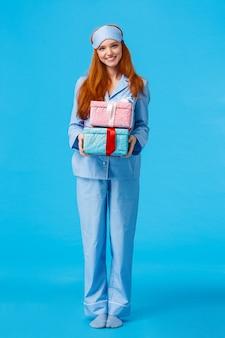 Wesoła i urocza młoda szczęśliwa ruda kobieta budzi się wcześnie wigilijnie, gratulując ferii zimowych, ubrana w piżamę i maskę snu, trzymając pudełka z prezentami, dając prezenty