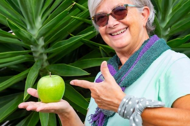 Wesoła i uśmiechnięta starsza kobieta z szalikiem i okularami przeciwsłonecznymi, trzymająca w ręku zielone jabłko. pojęcie zdrowego odżywiania i diety