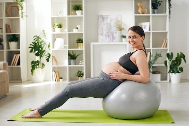 Wesoła i zdrowa młoda kobieta w ciąży, patrząc na ciebie podczas ćwiczeń na fitball na ścianie półek przy ścianie