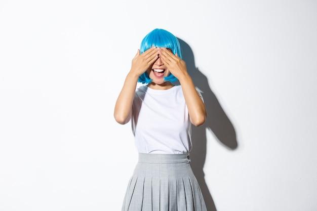 Wesoła imprezowa dziewczyna w niebieskiej peruce zamyka oczy rękami i uśmiecha się, czeka na niespodziankę, stoi.