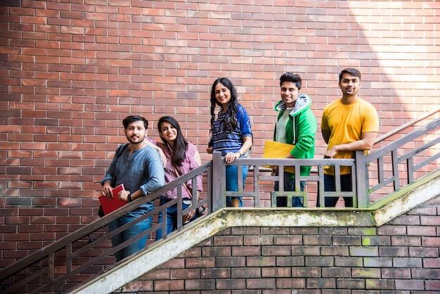 Wesoła indyjska azjatycka młoda grupa studentów lub przyjaciół spacerujących po kampusowym korytarzu lub po schodach