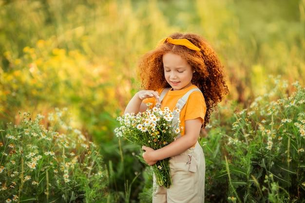 Wesoła, jędrna rudowłosa dziewczyna siedzi na kłodzie na letnim spacerze