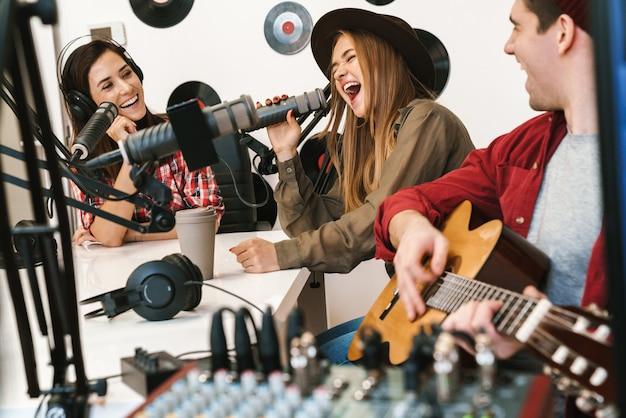 Wesoła kapela młodych muzyków grająca swoją piosenkę w sali radiowej z radiową prezenterką, audycja radiowa