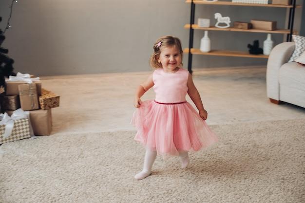 Wesoła kaukaska dziewczyna z krótkimi jasnymi falującymi włosami w ślicznej różowej sukience tańczy w pobliżu choinki w dużym jasnym pokoju
