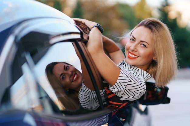 Wesoła kaukaska kobieta jedzie przez malownicze słoneczne miasto i macha rękami, wyciągając się przez okno samochodu w piękny dzień