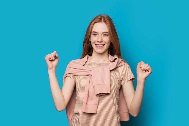 Wesoła kaukaska kobieta z rudymi włosami i pięknymi piegami gestykuluje znak władzy pokryty swetrem na niebieskim tle