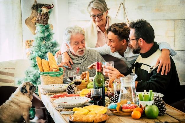 Wesoła kaukaska rodzina cieszy się i świętuje razem w domu przy stole pełnym świątecznych ozdób