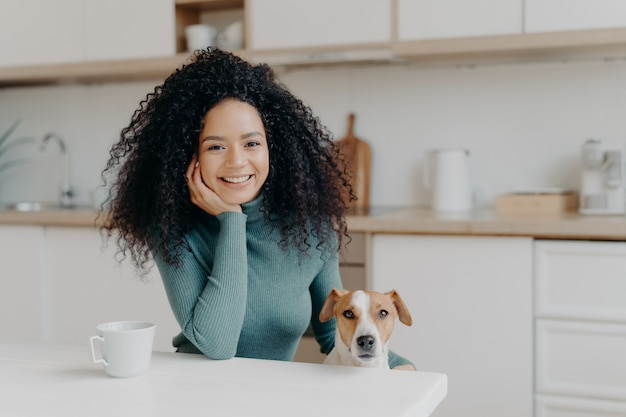 Wesoła kędzierzawa kobieta siedzi w kuchni, pije gorącą wodę, a jej lojalne zwierzę domowe pozuje cieszyć się spędzaniem razem czasu