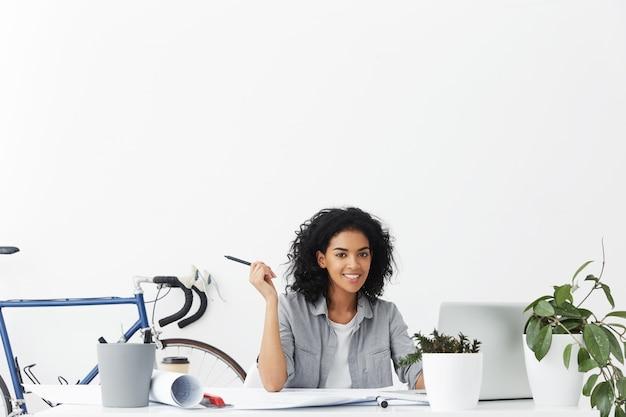 Wesoła kobieta architekt trzymając ołówek i wyłączając notebooka