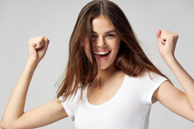 Wesoła kobieta biała koszulka emocji ręce zaciśnięte w pięść