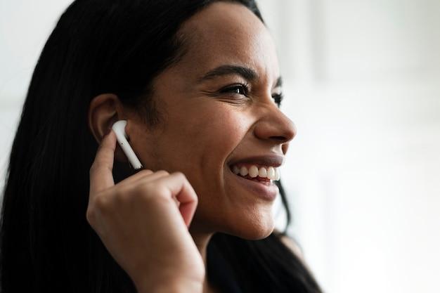 Wesoła kobieta ciesząca się muzyką przez bezprzewodowe słuchawki