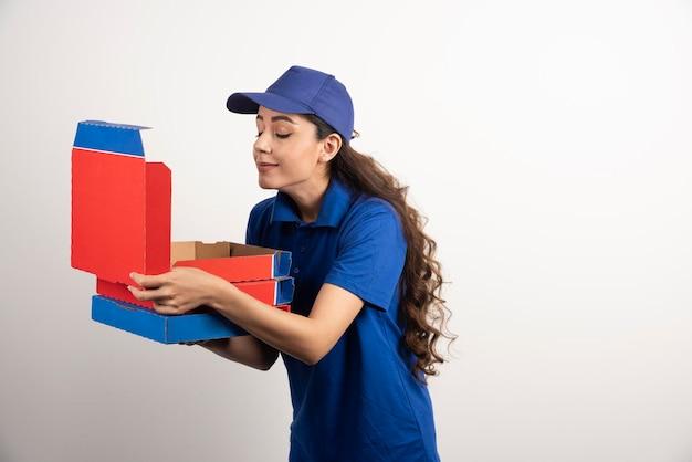 Wesoła kobieta dostarczająca pizzę w niebieskim mundurze wącha jedno z pudełek. zdjęcie wysokiej jakości